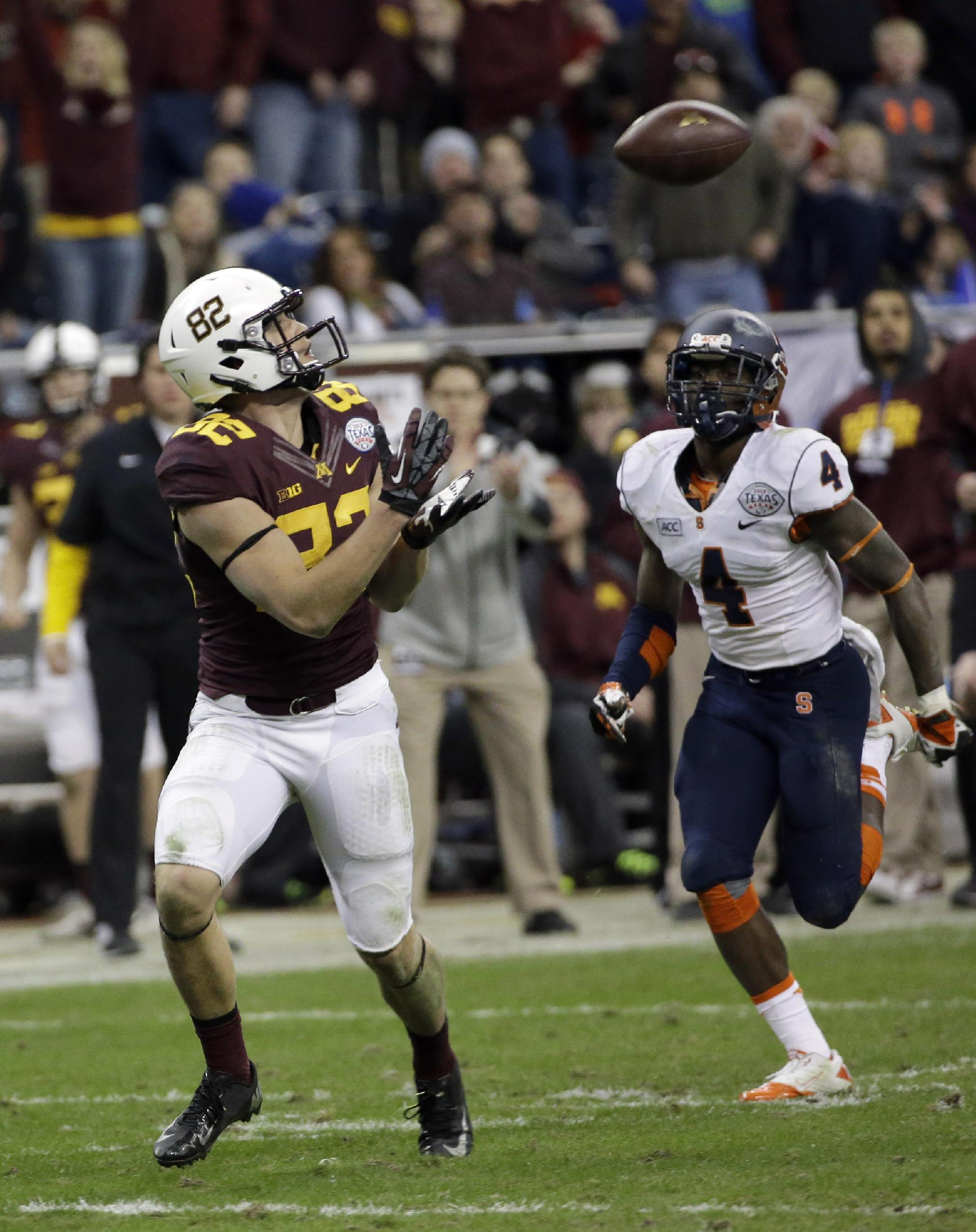 Minnesota wide receiver Drew Wolitarsky (82) catches a pass for a touchdown as Syracuse cornerback Brandon Reddish (4) defends during the second half of the Texas Bowl NCAA college football game on Friday, Dec. 27, 2013, in Houston. Syracuse won 21-17