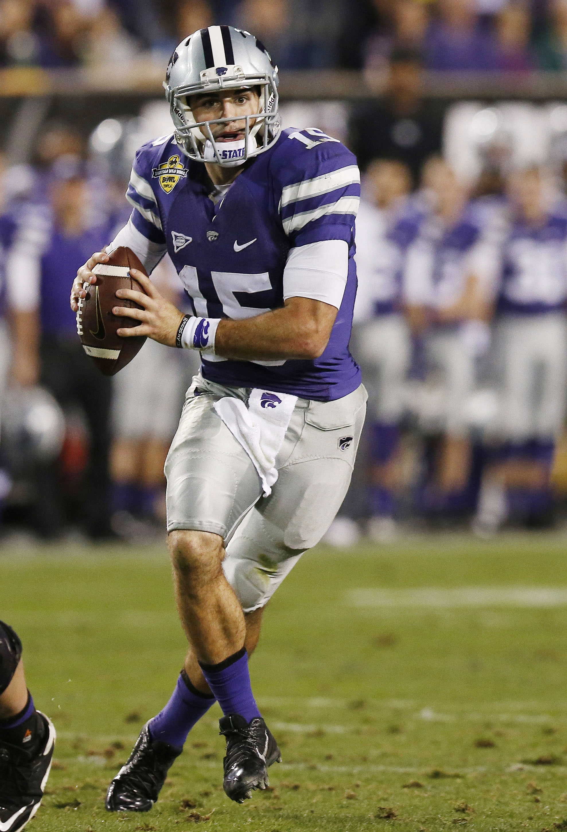 Kansas State's Jake Waters rolls out to pass the ball against Michigan during the second half of the Buffalo Wild Wings Bowl NCAA college football game, Saturday, Dec. 28, 2013, in Tempe, Ariz. Kansas State defeated Michigan 31-14