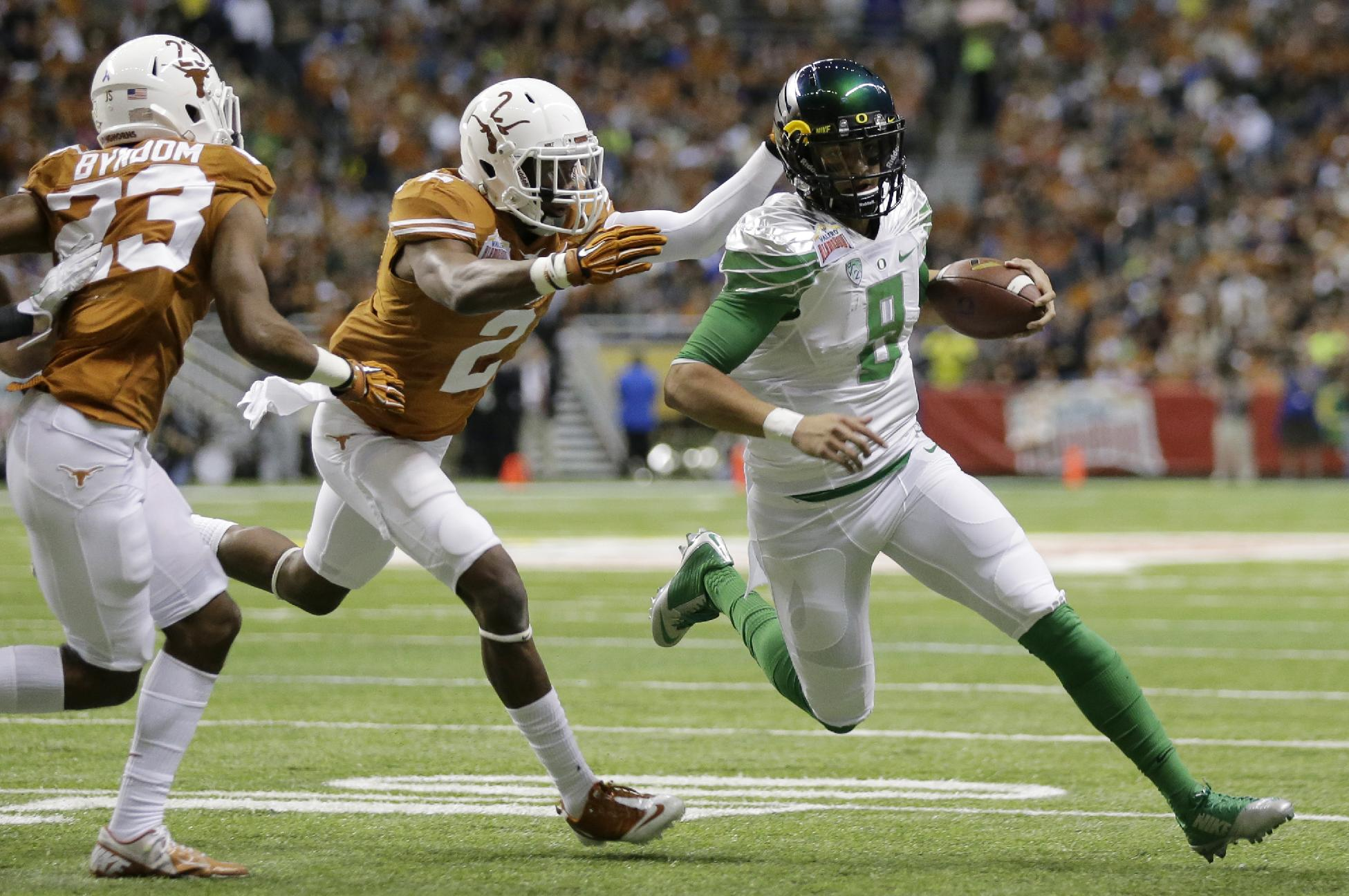 Oregon's Marcus Mariota (8) is chased by Texas' Mykkele Thompson (2) during the first quarter in the Valero Alamo Bowl NCAA college football game, Monday,  Dec. 30, 2013, in San Antonio
