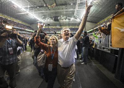 Texas head coach Mack Brown heads off the field as the head coach for the last time with his wife Sally Mack after losing against Oregon Ducks 30-7  in the Valero Alamo Bowl at Alamdome in San Antonio, Monday, Dec. 30, 2013