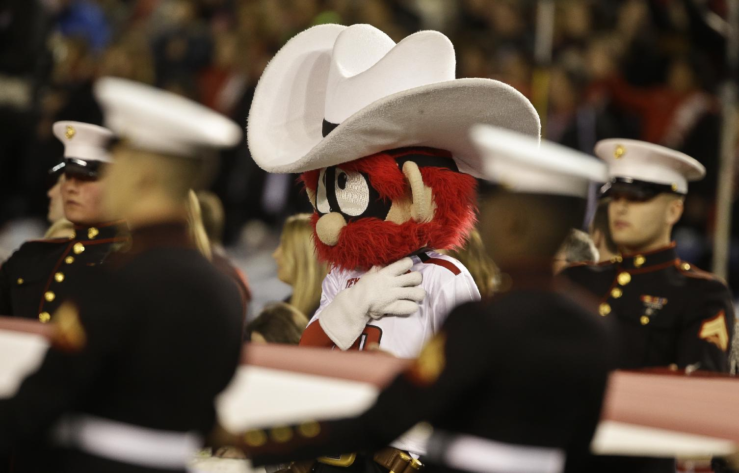 The Texas Tech Red Raider mascot stands with United States Marines during the playing of the Star Bangled Banner in pre-game activities at the Holiday Bowl NCAA college football football game Monday, Dec. 30, 2013, in San Diego