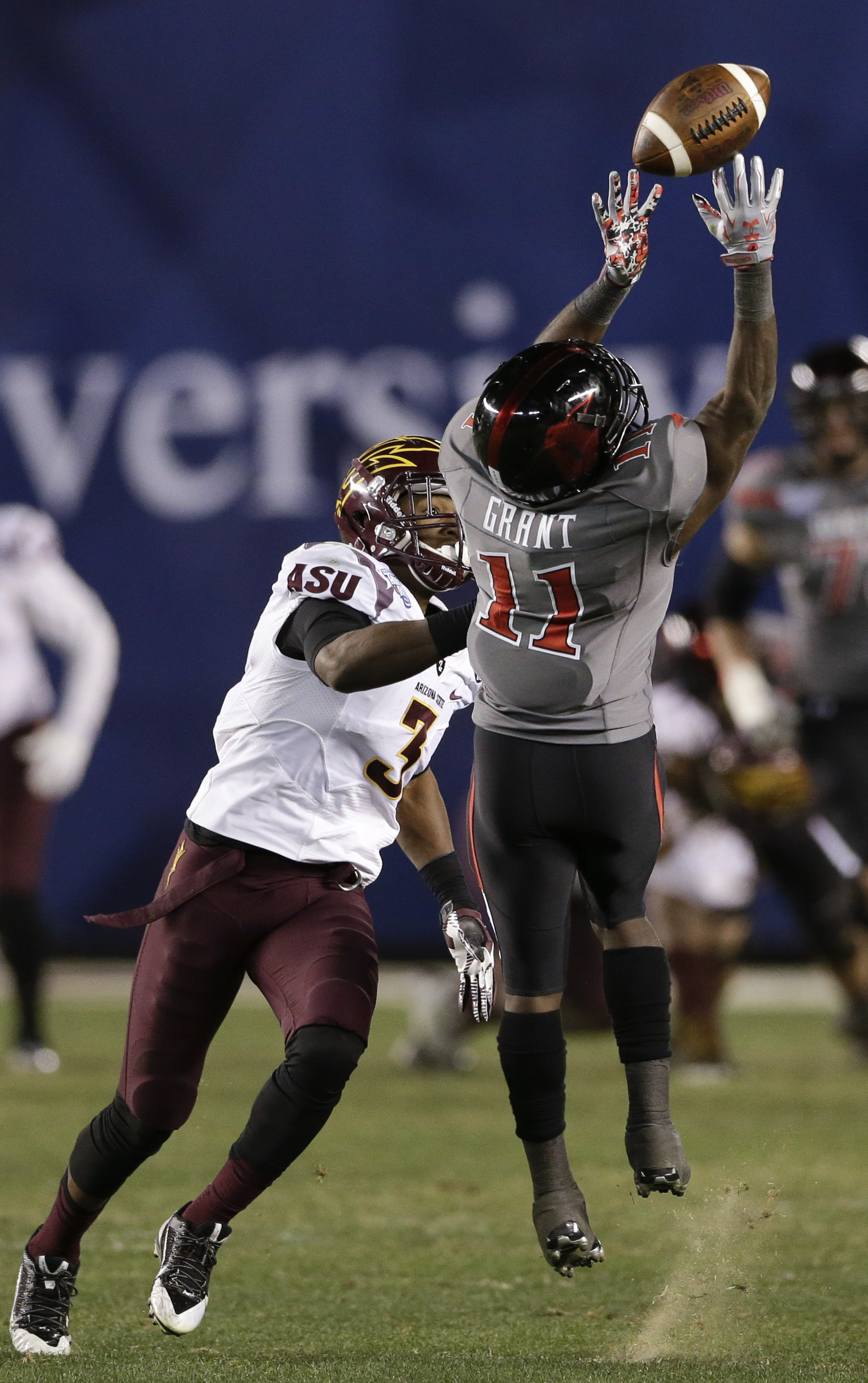 Texas Tech wide receiver Jakeem Grant (11) can't hold on to a pass as Arizona State defensive back Damarious Randall, left, defends during the second half of the Holiday Bowl NCAA college football game Monday, Dec. 30, 2013, in San Diego