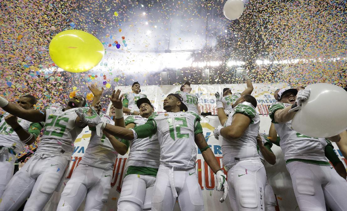 Oregon players celebrate the team's win over Texas in the Valero Alamo Bowl NCAA college football game, Monday, Dec. 30, 2013, in San Antonio. Oregon won 30-7