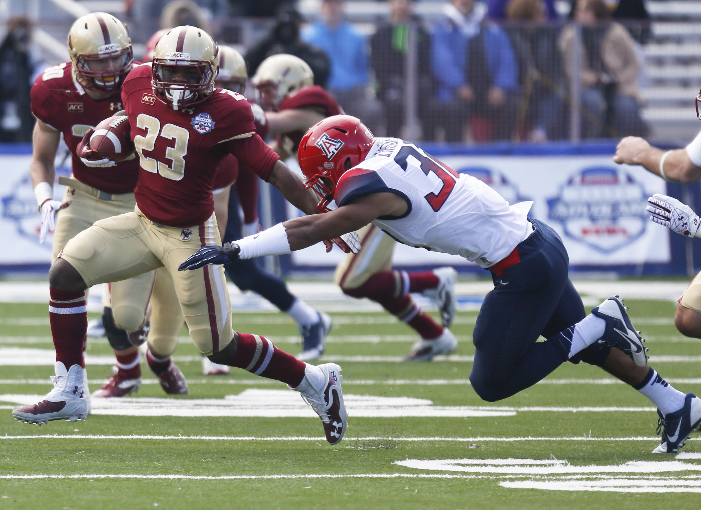 Boston College running back Myles Willis (23) runs for a short gain against the defense of Arizona linebacker DeAndre' Miller (32) during the first half of the AdvoCare V100 Bowl NCAA college football game, Tuesday, Dec. 31, 2013, at Independence Stadium in Shreveport, La