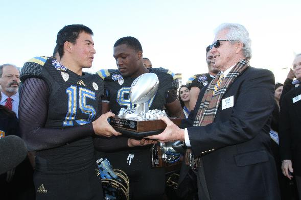 UCLA kicker Ka'imi Fairbaim, left,  was awarded the Most Valuable Special Teams Player by John Folmer after defeating Virginia Tech 42-12 in an NCAA college football game Tuesday Dec. 31, 2013, in El Paso, Texas