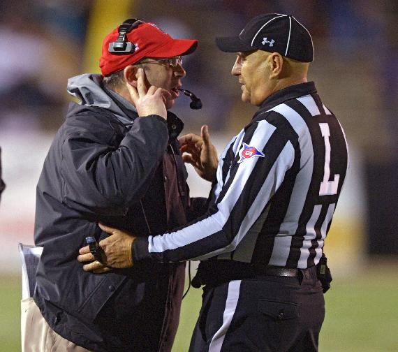 Ball State head coach Pete Lembo, left, talks with linesman Tim Sistrunk after a Ball State score against Arkansas State in the first quarter of the GoDaddy Bowl NCAA college football game, Sunday, Jan. 5, 2014, in Mobile, Ala
