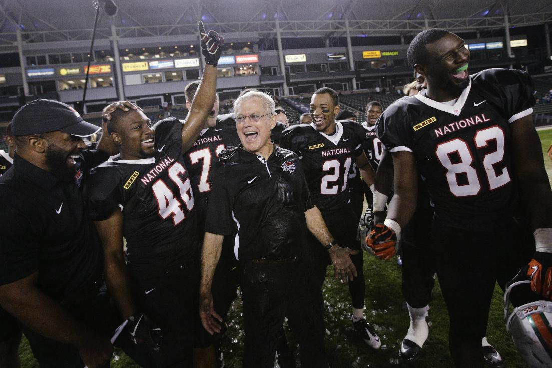 National team coach Dick Vermeil, center, and players Ray Agnew(46), of Southern Illinois; Josh Wells (71), of James Madison; Martin Mayless Jr. (21), of Central Methodist; and Asante Cleveland( 82), of Miami, celebrate their team's 31-17 win against the American team in he NFLPA Collegiate Bowl football game Saturday, Jan. 18, 2014, in Carson, Calif