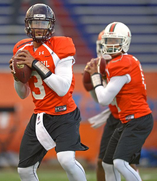 North Squad quarterback Logan Thomas of Virginia Tech (3) drops back with fellow quarterbacks Tajh Boyd of Clemson (10), middle, and Stephen Morris of Miami (17), right, during Senior Bowl practice at Ladd-Peebles Stadium, Monday, Jan. 20, 2014, in Mobile, Ala