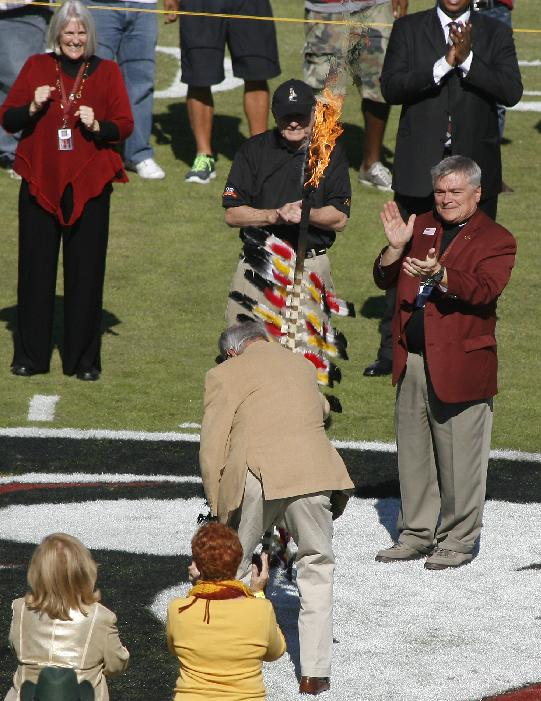As Florida State president Eric Barron, right, and his wife Molly, top left, applaud, former Florida State head coach Bobby Bowden, center, plants the spear on the 50-yard line before an NCAA college football game against North Carolina State, Saturday, Oct. 26, 2013, in Tallahassee, Fla