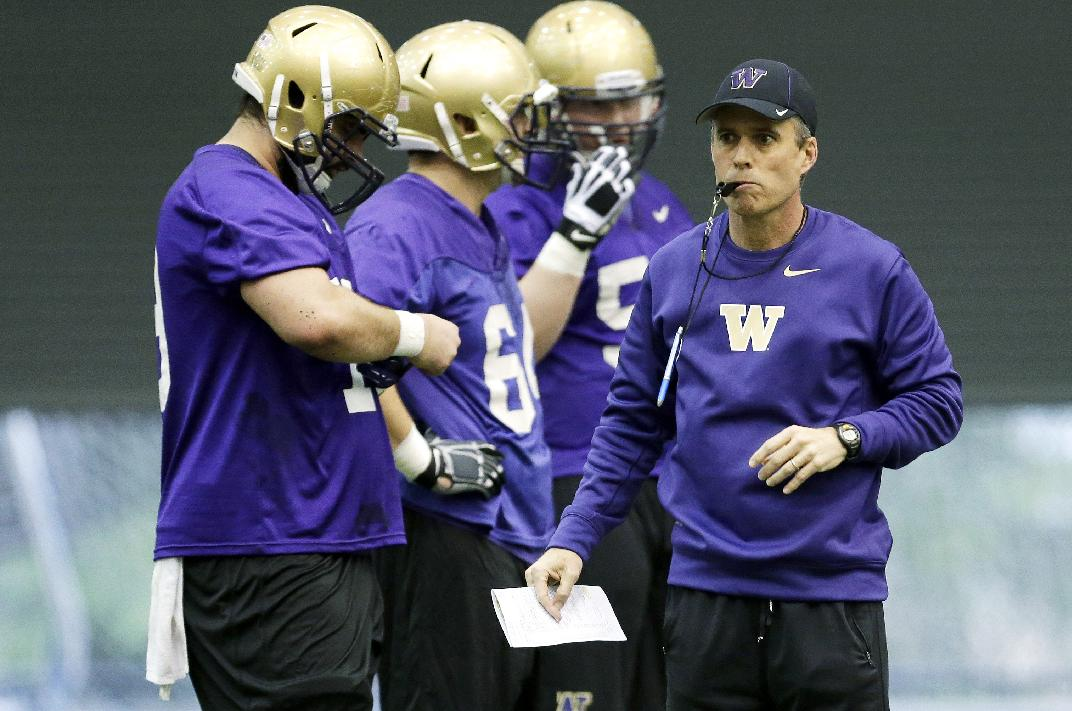 New Washington head football coach Chris Petersen, right, blows his whistle on the first day of spring NCAA college football practice, Tuesday, March 4, 2014, in Seattle