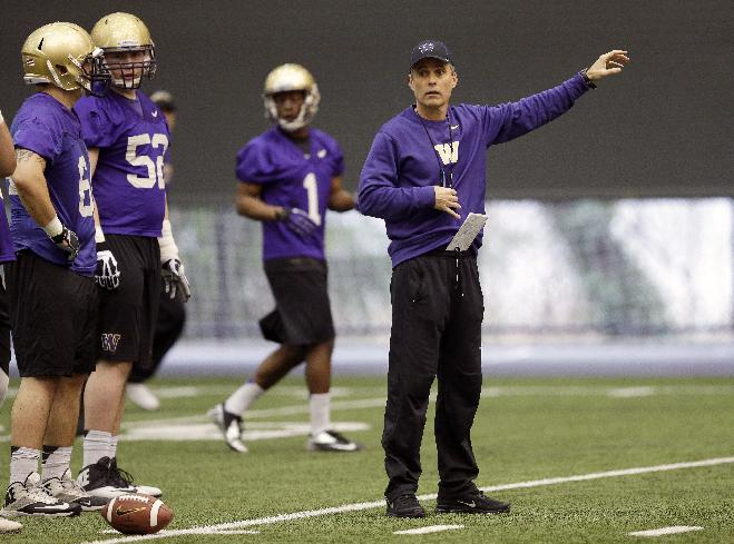 New Washington head football coach Chris Petersen, right, gives directions to his team on the first day of spring NCAA college football practice, Tuesday, March 4, 2014, in Seattle