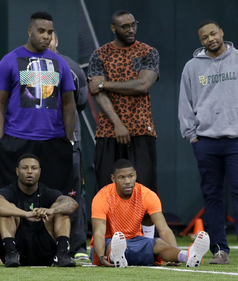 Former Baylor player and current Dallas Cowboys wide receiver Terrance Williams, front right, sits with current and former players as they watch athletes participate during pro day for NFL football representatives at the university on Wednesday, March 19, 2014, in Waco, Texas