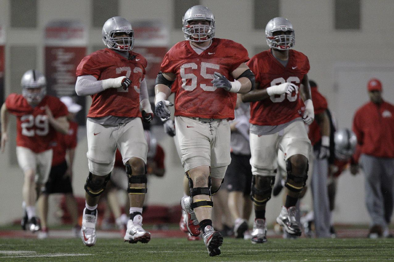 In this March 4, 2014 file photo, Ohio State offensive lineman Pat Elflein (65) runs drills during an NCAA college football practice in Columbus, Ohio. On a team that had a Heisman Trophy candidate at quarterback and a 1,500-yard rusher at tailback, Urban Meyer always said the strength of Ohio State's offense a year ago was it's brawny offensive line. Now four-fifths of that front wall has graduated and some major reconstruction project is taking place