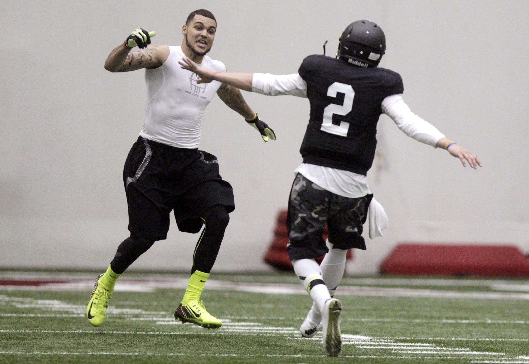 Texas A&M quarterback Johnny Manziel (2) and wide receiver Mike Evans celebrate after a pass reception during a drill at pro day for NFL football representativesin College Station, Texas, Thursday, March 27, 2014