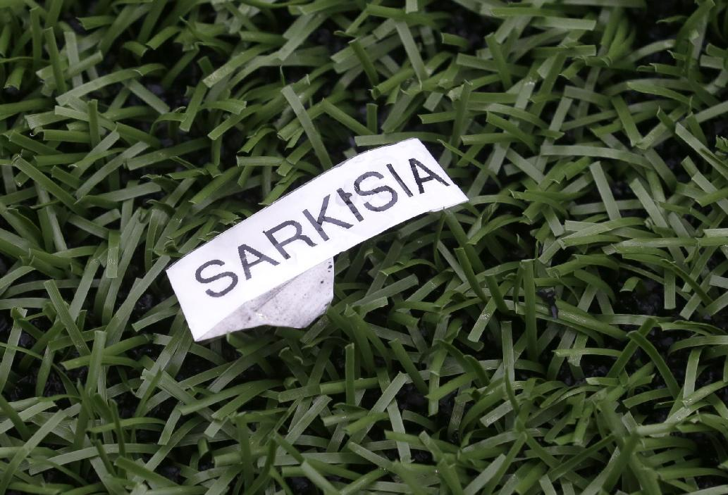 A discarded label bearing the name of Steve Sarkisian, former Washington head football coach, rests on the turf Saturday, April 19, 2014, during Washington's spring NCAA college football preview in Seattle under the direction of coach Chris Petersen. Sarkisian left Washington at the end of the regular season to take the head football coach position at Southern California