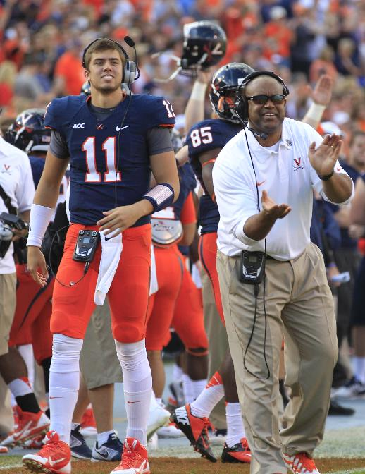 Virginia quarterback Greyson Lambert (11) and coach Mike London cheer the team during the first half of an NCAA college football game in Charlottesville, Va., Saturday, Nov. 2, 2013