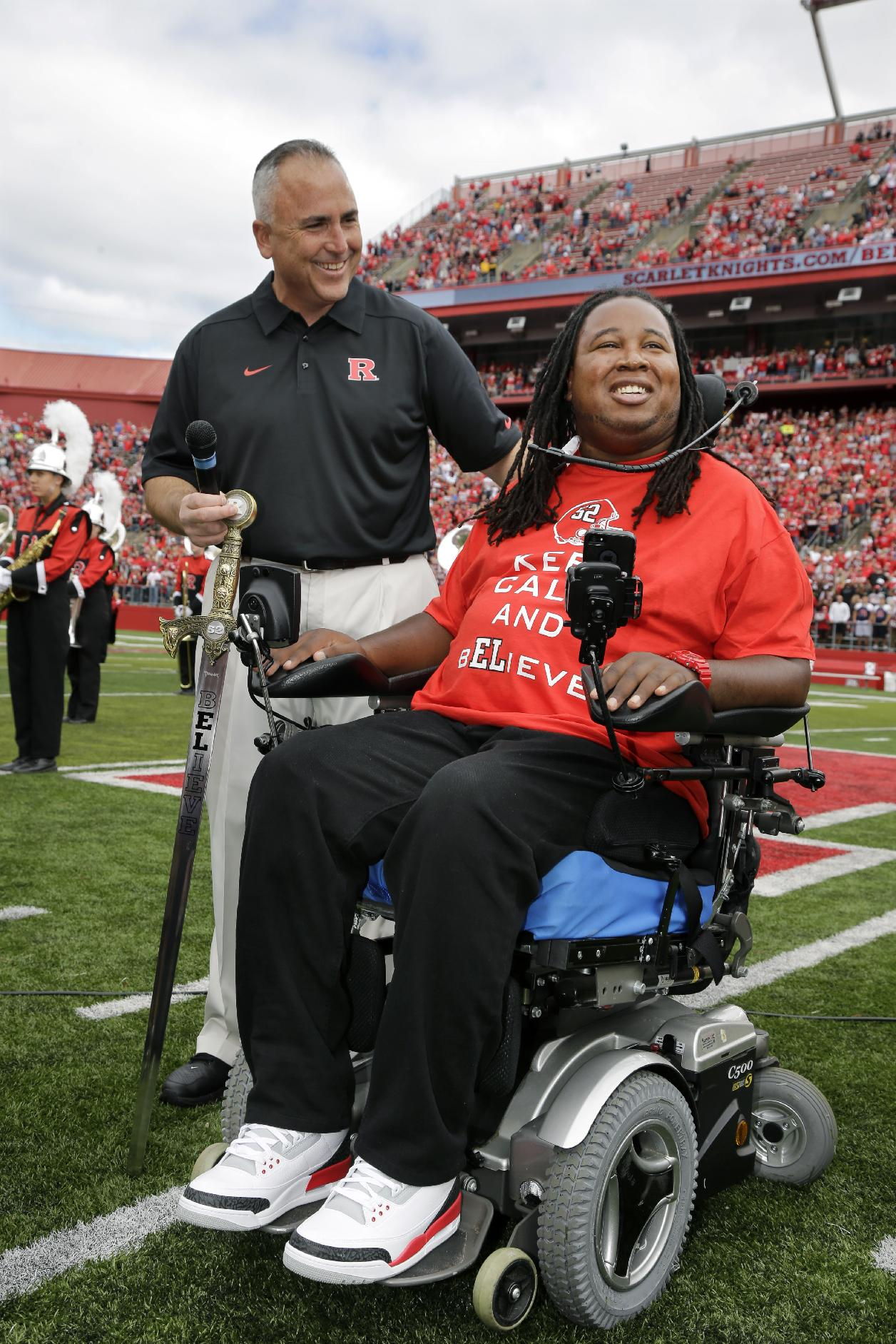 Rutgers football head coach Kyle Flood holds a Rutgers sword presented to former football player Eric LeGrand during ceremony where his jersey number 52 was retired at halftime of an NCAA college football game against Eastern Michigan in Piscataway, N.J., Saturday, Sept. 14, 2013