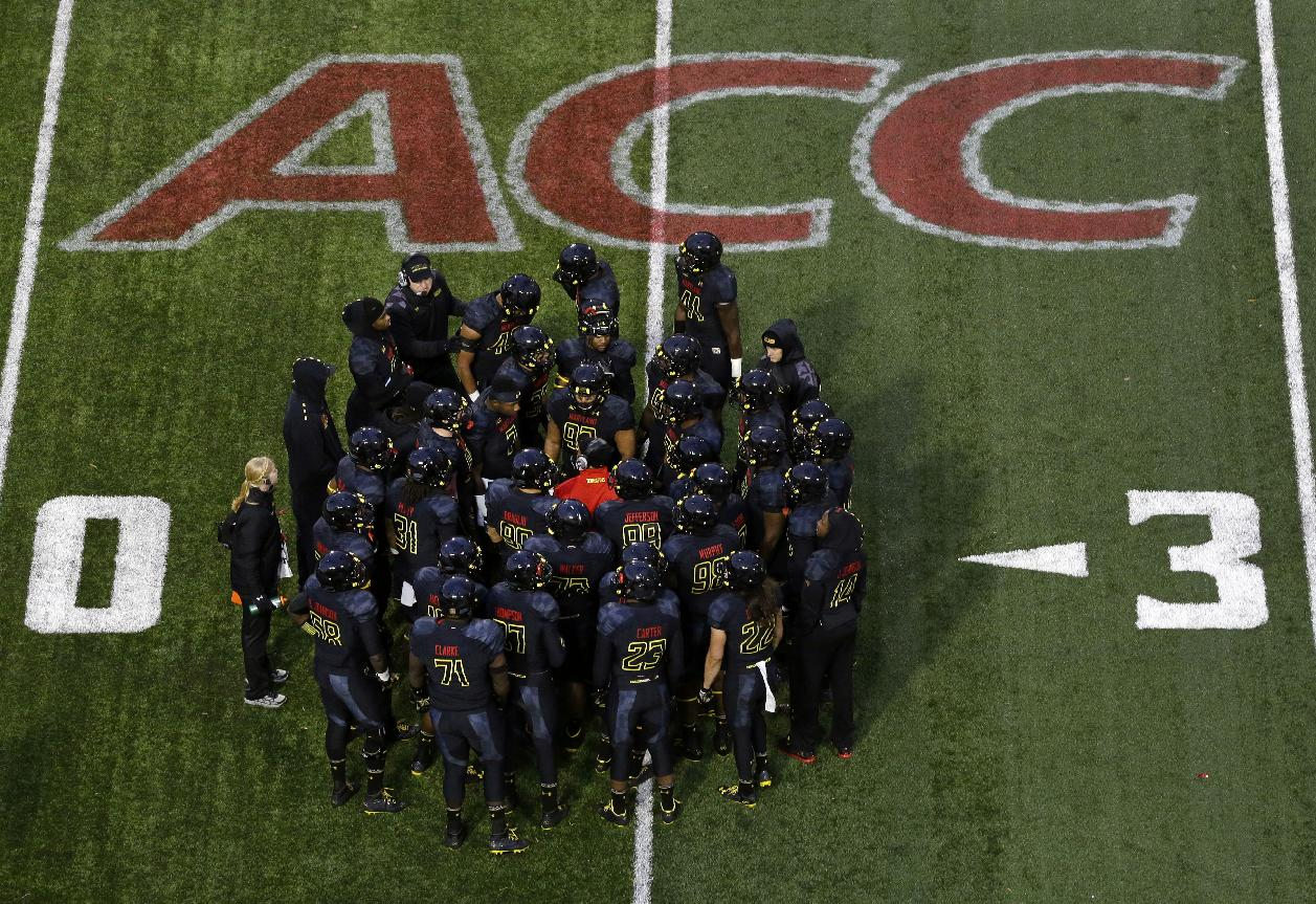 File-This Nov. 23, 2013, file photo shows members of the Maryland football team huddling in the first half of an NCAA college football game against Boston College in College Park, Md.  The musical chairs of conference realignment returns this this week, with more major colleges taking new seats. On Tuesday, July 1, 2014, 12 FBS teams officially switch places, including Louisville in the Atlantic Coast Conference and Maryland and Rutgers in the Big Ten