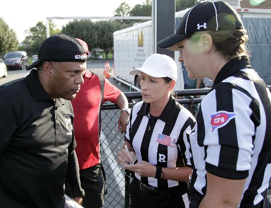 In a photo provided by the NFL, Houston coach Brian Wiggins listens as referee Shannon Eastin, center, and official Catherine Conti give pre-game instructions at the International Women's Football League Championships, Saturday, July 26, 2014. in Rock Hill, S.C. The 38-year-old Conti had been assigned to the Southeast Missouri State-Kansas game on Sept. 6, making her the first woman to work a football game in the Big 12 Conference. Conti will work mostly as a line judge in the Mountain West for the second straight year. She landed the Big 12 gig through the league's officiating partnership with the Mountain West and FCS-level Southland Conference