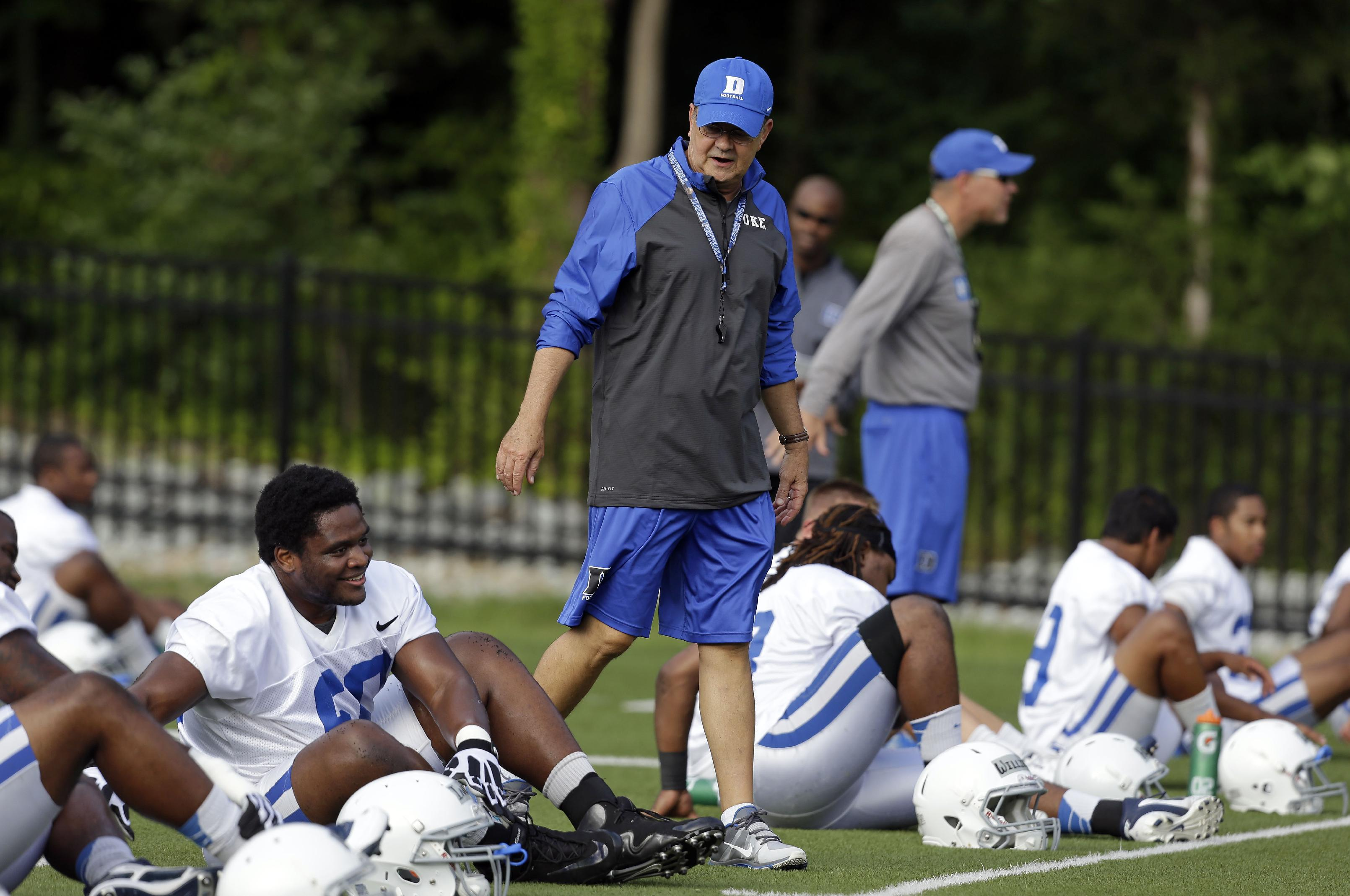 In this Monday, Aug. 5, 2013, file photo, Duke coach David Cutcliffe chats with players as they stretch during an NCAA college football practice in Durham, N.C. A growing number of college coaches are watching the social media behavior of student athletes, including Cutcliffe