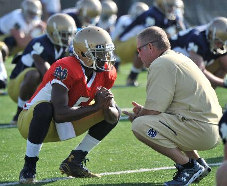In this Aug. 9, 2014, file photo, Notre Dame coach Brian Kelly, right, talks with quarterback Everett Golson during practice in South Bend, Ind. Golson has reclaimed the job as Notre Dame's starting quarterback after being suspended last semester for academic impropriety. Coach Brian Kelly on Wednesday, Aug. 13, 2014, said Golson would start against Rice on Aug. 30 and said he hopes he will be the starter for the entire season