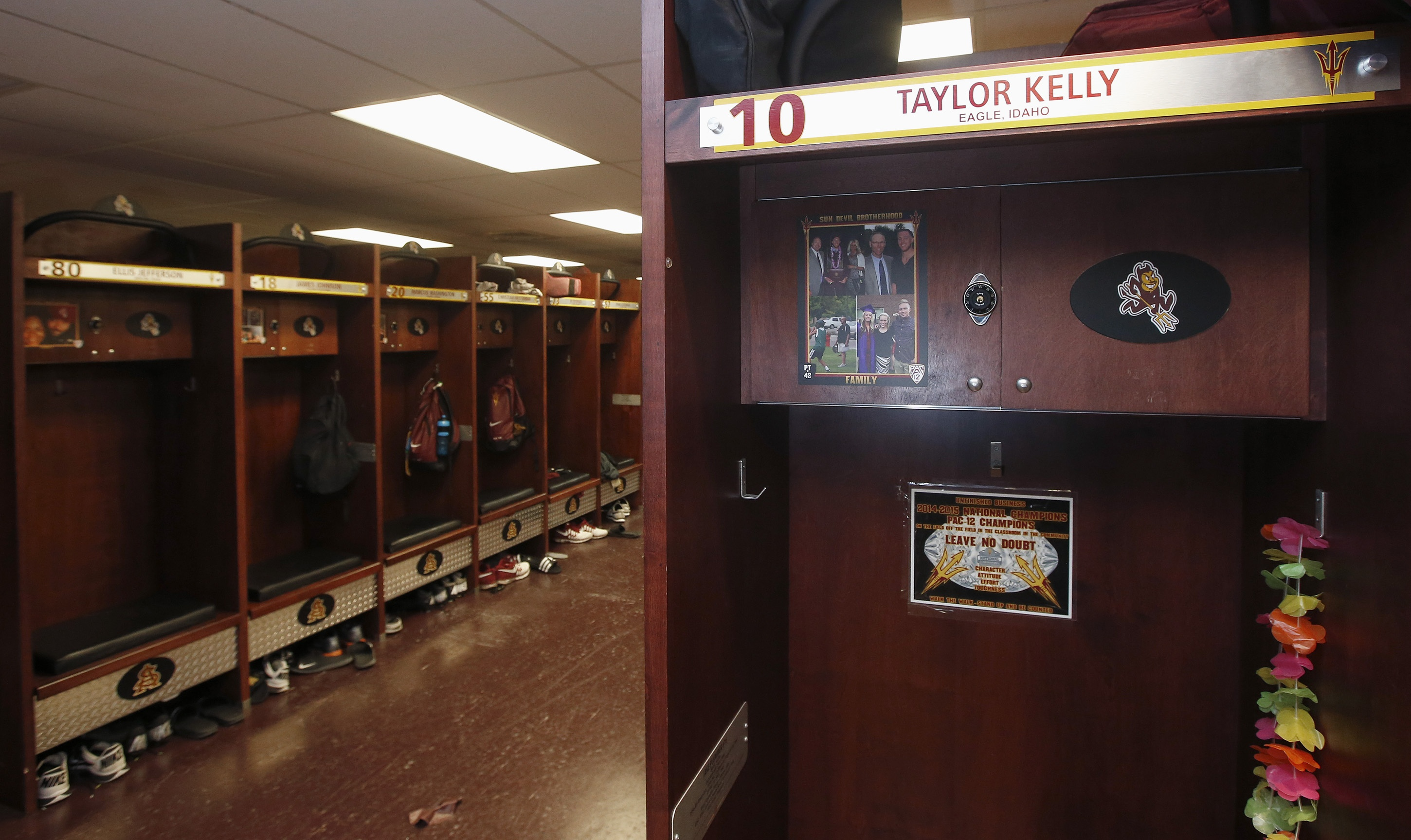 Arizona State quarterback Taylor Kelly has a variety of photos of his family at his locker in the Arizona State football team locker room Monday, Aug. 11, 2014, in Tempe, Ariz.  Each player and coach on Arizona State's team has a photo above their locker of someone who has inspired them. There are mothers, fathers, siblings, grandparents, a few coaches. Coach Todd Graham had them all do it so they can remember it's not just their teammates they're playing for
