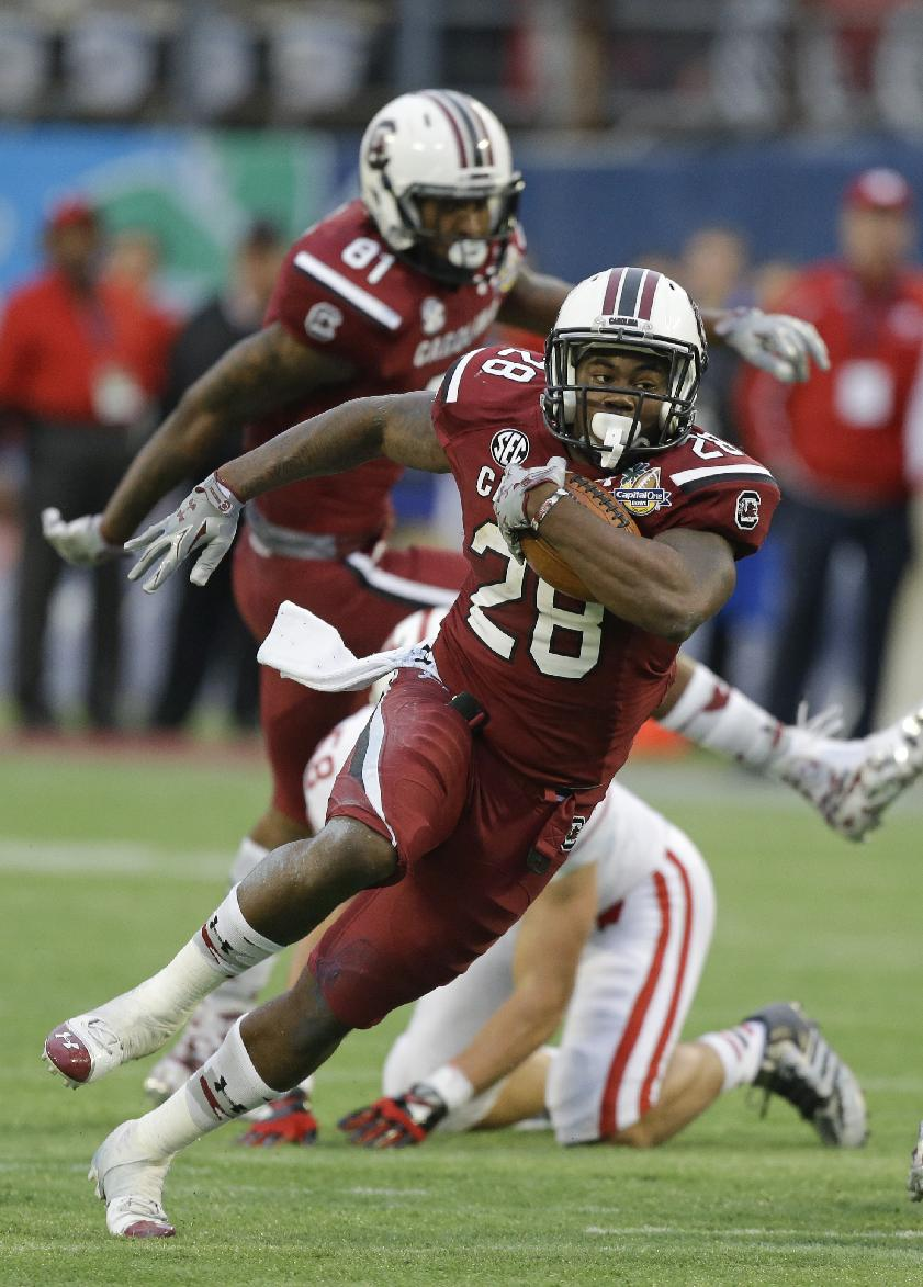 In this Jan. 1, 2014, file photo, South Carolina running back Mike Davis (28) gains yardage against Wisconsin during the second half of the Capital One Bowl NCAA college football game in Orlando, Fla. Steve Spurrier says 1,000-yard rusher Mike Davis hasn't practiced this week and might not be ready when the ninth-ranked Gamecocks open the season against No. 21 Texas A&M in a week
