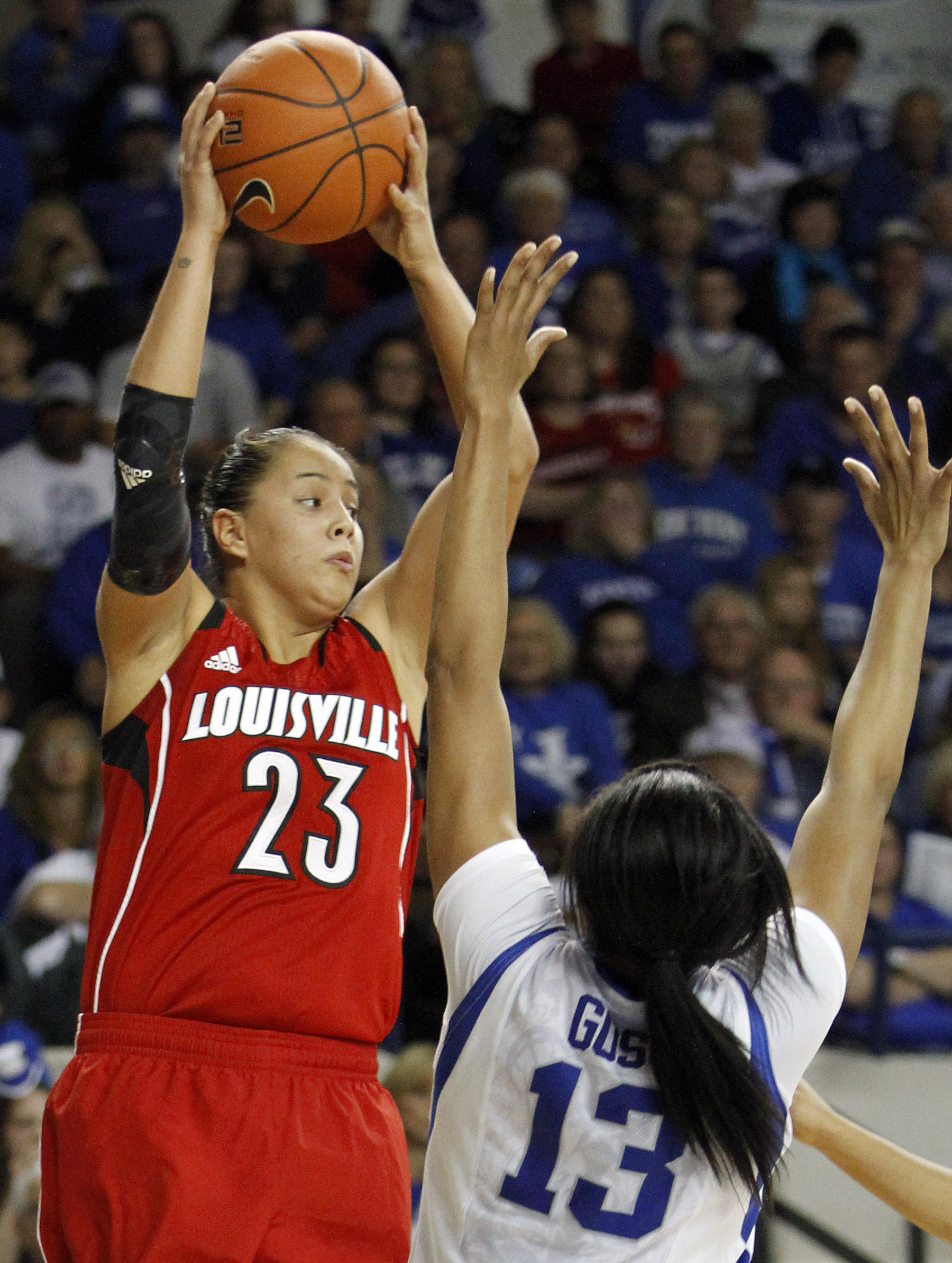 Louisville's Shoni Schimmel (23) looks to pass while under pressure from Kentucky's Bria Goss during the second half of an NCAA college basketball game, Sunday, Dec. 1, 2013, in Lexington, Ky. Kentucky won 69-64