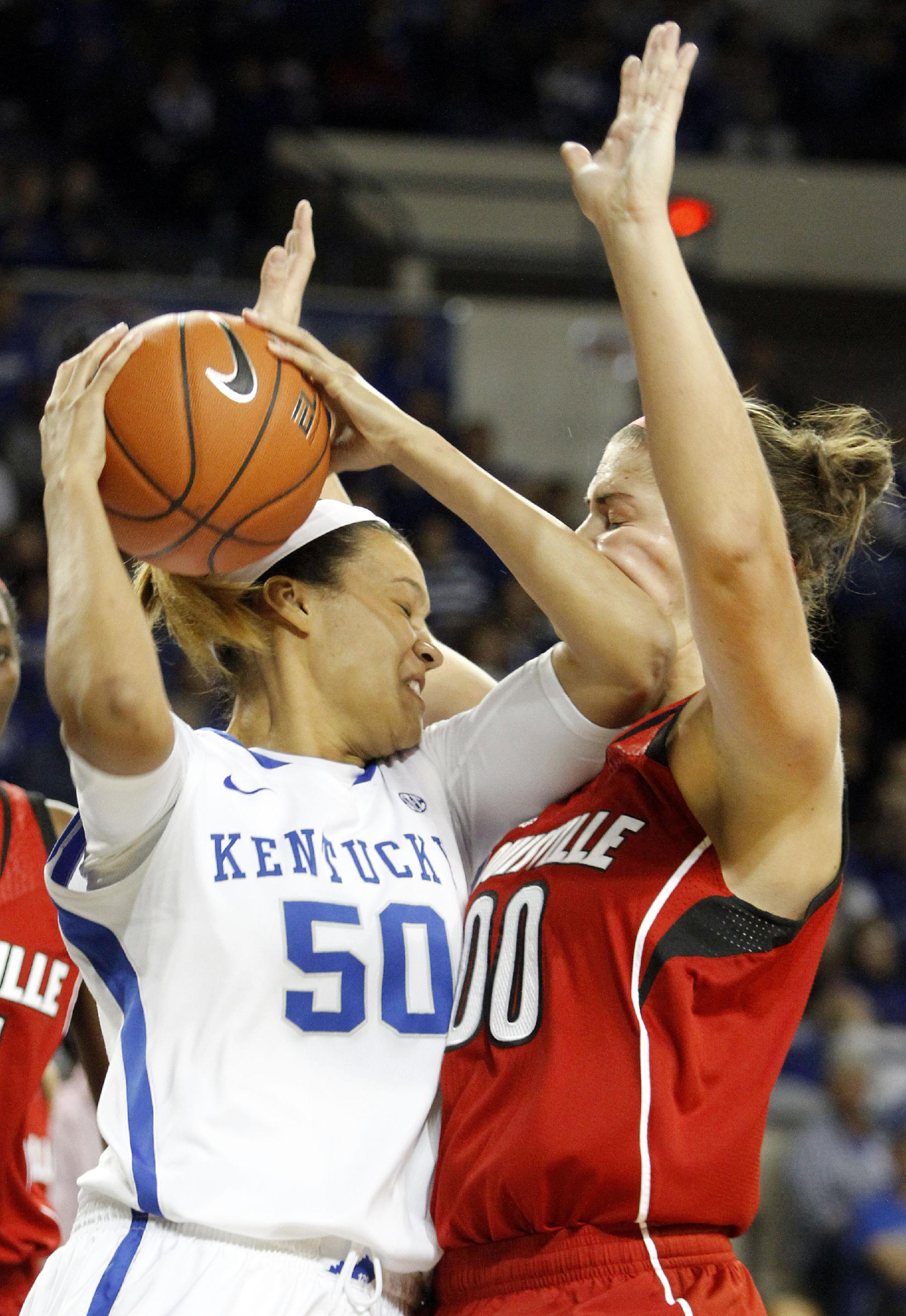Kentucky's Azia Bishop (50) pulls down a rebound and is called for a foul next to Louisville's Sara Hammond (00) during the first half of an NCAA college basketball game on Sunday, Dec. 1, 2013, in Lexington, Ky