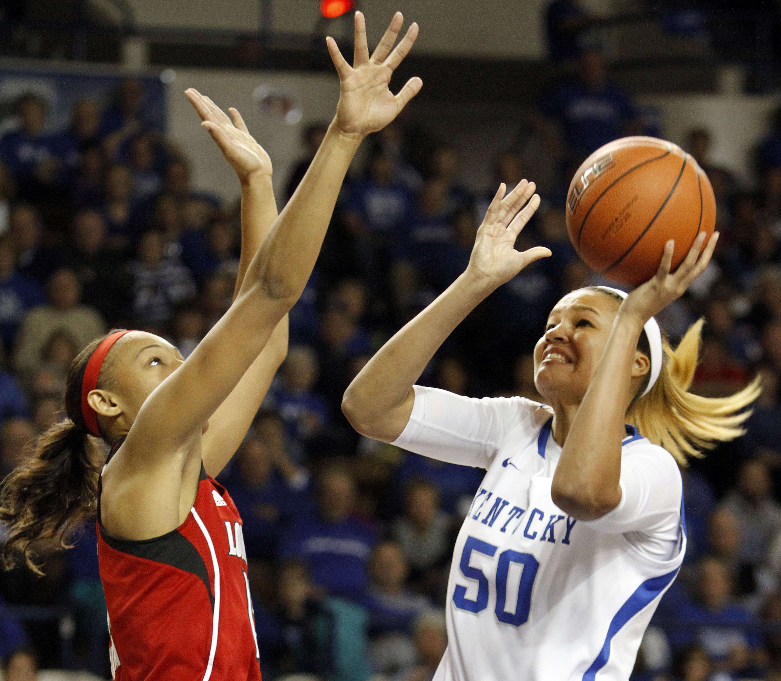 Kentucky's Azia Bishop (50) shoots under pressure from Louisville's Cortnee Walton during the first half of an NCAA college basketball game on Sunday, Dec. 1, 2013, in Lexington, Ky