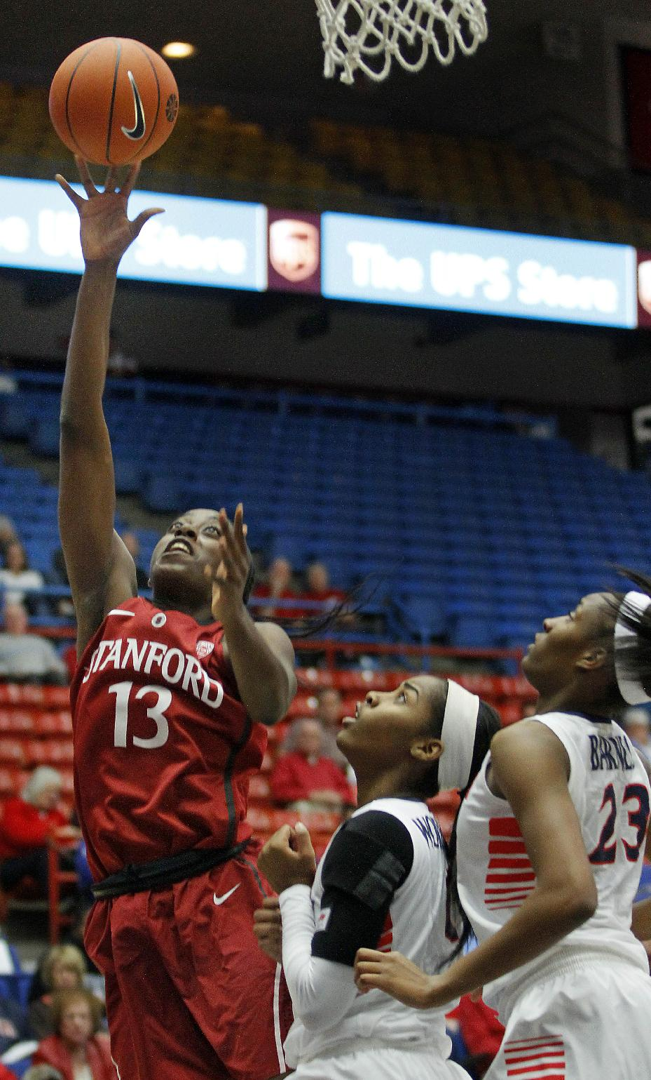 Stanford's Chiney Ogwumike (13) goes to the basket while Arizona's Breanna Workman, center, and Erica Barnes (23) watch in the first half of an NCAA college basketball game on Friday, Jan. 17, 2014, in Tucson, Ariz
