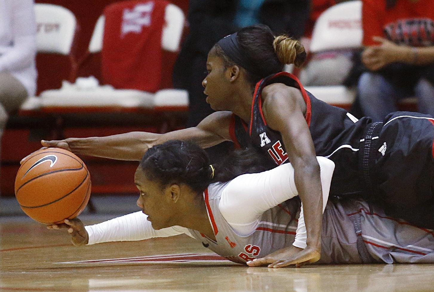 University of Houston forward Destini Texada, bottom, and Louisville guard Monny Niamke dive for a loose ball during the second half of an NCAA women's basketball game, Tuesday, Jan. 21, 2014, in Houston