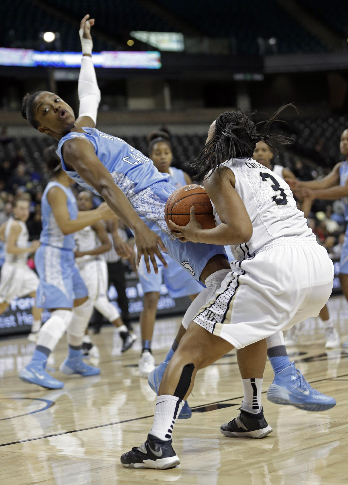 North Carolina's Diamond DeShields, left, is knocked down by Wake Forest's Ataijah Taylor, right, during the first half of an NCAA college basketball game in Winston-Salem, N.C., Thursday, Jan. 23, 2014. Taylor was charged with a foul