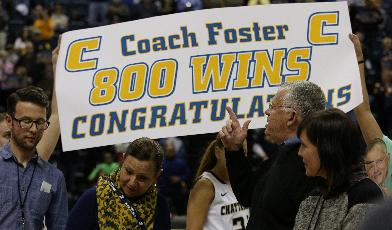 Tennessee-Chattanooga women's basketball team presents a banner celebrating head coach Jim Foster, second from right, after his 800th coaching career win Saturday, Jan. 25, 2014, at McKenzie Arena in Chattanooga, Tenn. The Lady Mocs won 63-50 over Samford