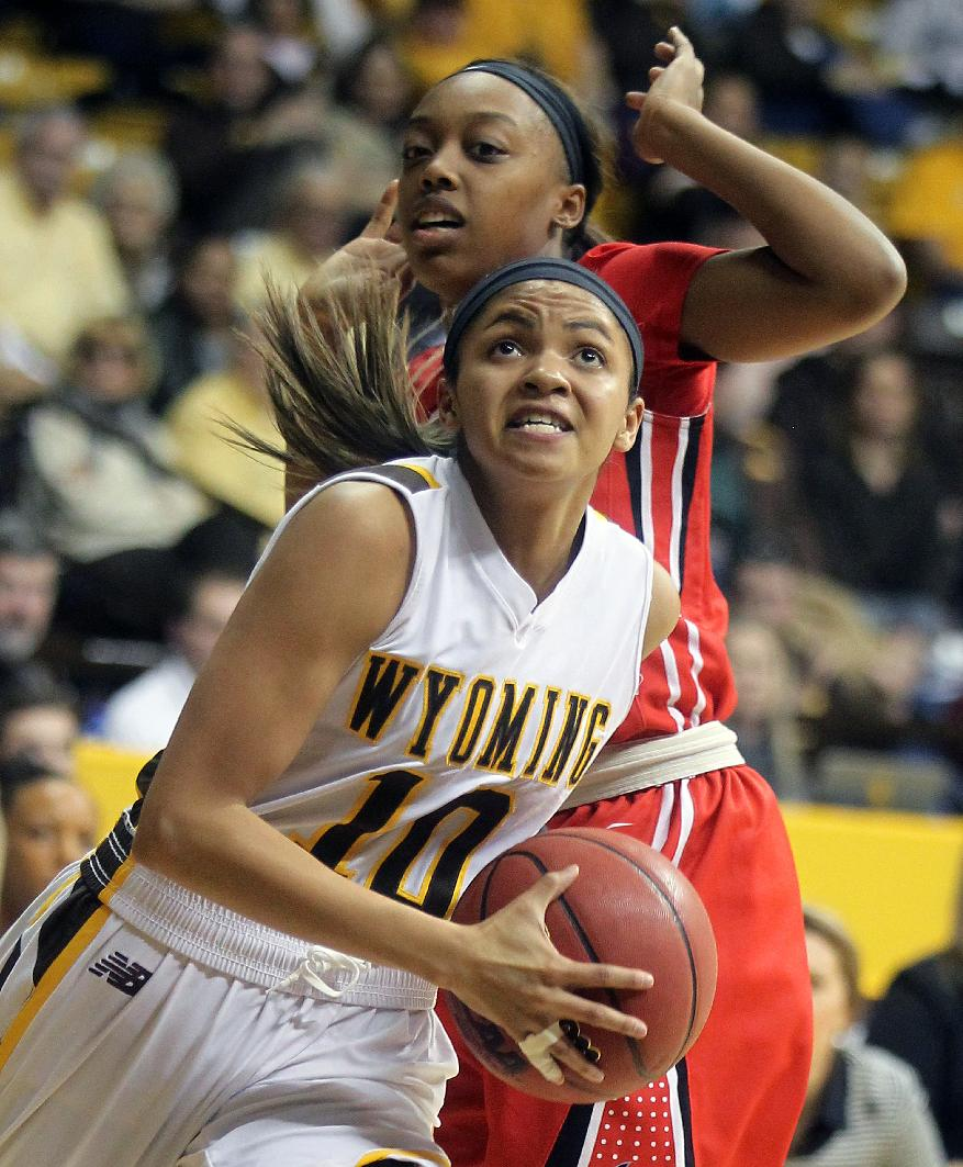 Wyoming's Marquelle Dent drives to the basket past UNLV's Briana Charles in the first half of an NCAA college basketball game, Saturday, Feb. 8, 2014, in Laramie, Wyo