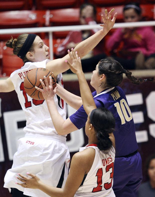 Utah forward Michelle Plouffe, left, and Utah guard Devri Owens (13) defend Washington guard Kelsey Plum (10) during an NCAA college basketball game in Salt Lake City, Sunday, Feb. 16, 2014