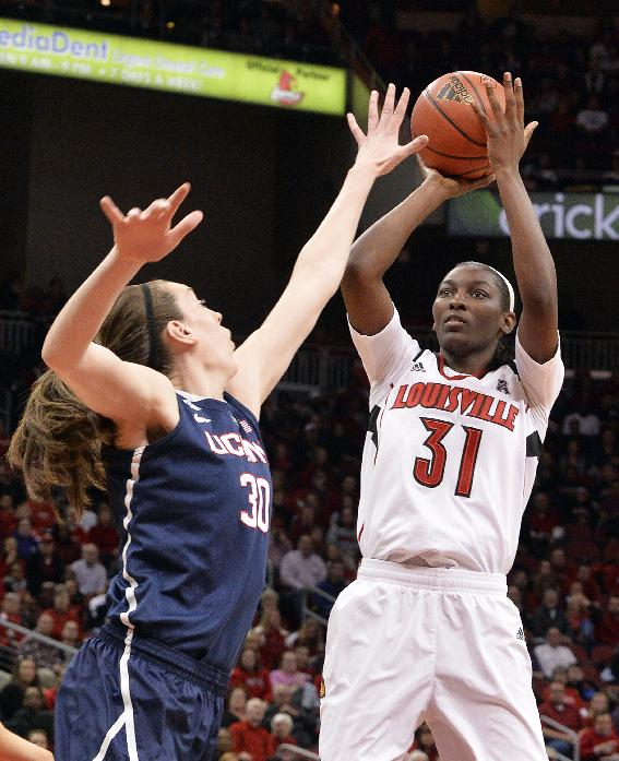 Louisville's Asia Taylor, right, puts up a shot over the defense of Connecticut's Breanna Stewart during the first half of an NCAA college basketball game, Monday, March 3, 2014, in Louisville, Ky