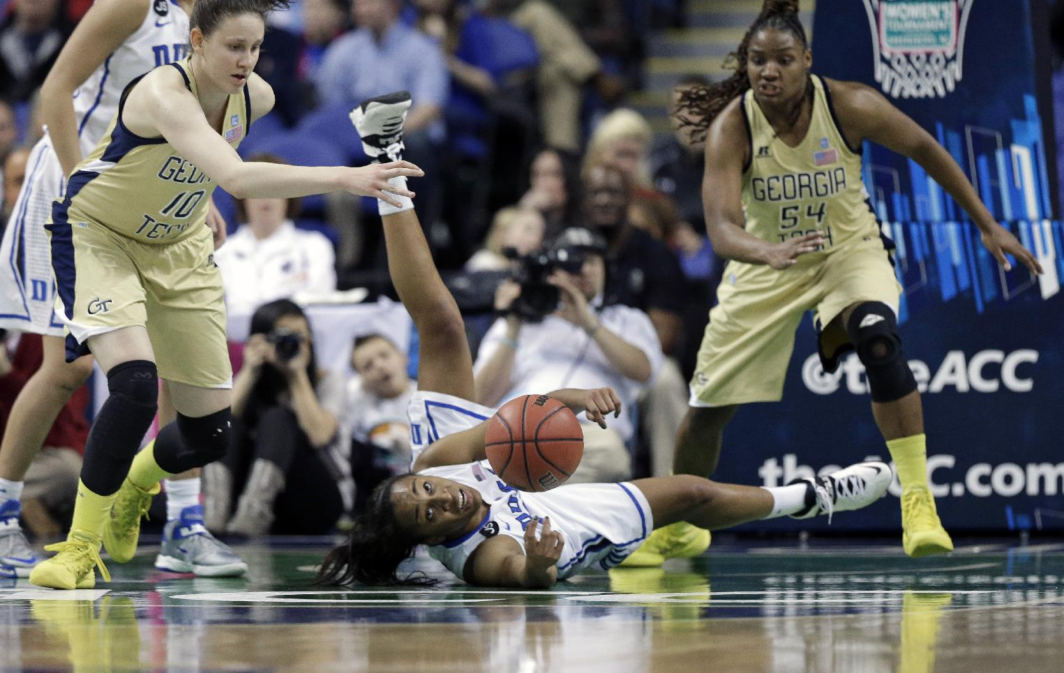 Duke's Oderah Chidom, center, passes the ball as Georgia Tech's Katarina Vuckovic, left, and Roddreka Rogers, right, defend during the first half of an NCAA college basketball game at the Atlantic Coast Conference tournament in Greensboro, N.C., Friday, March 7, 2014