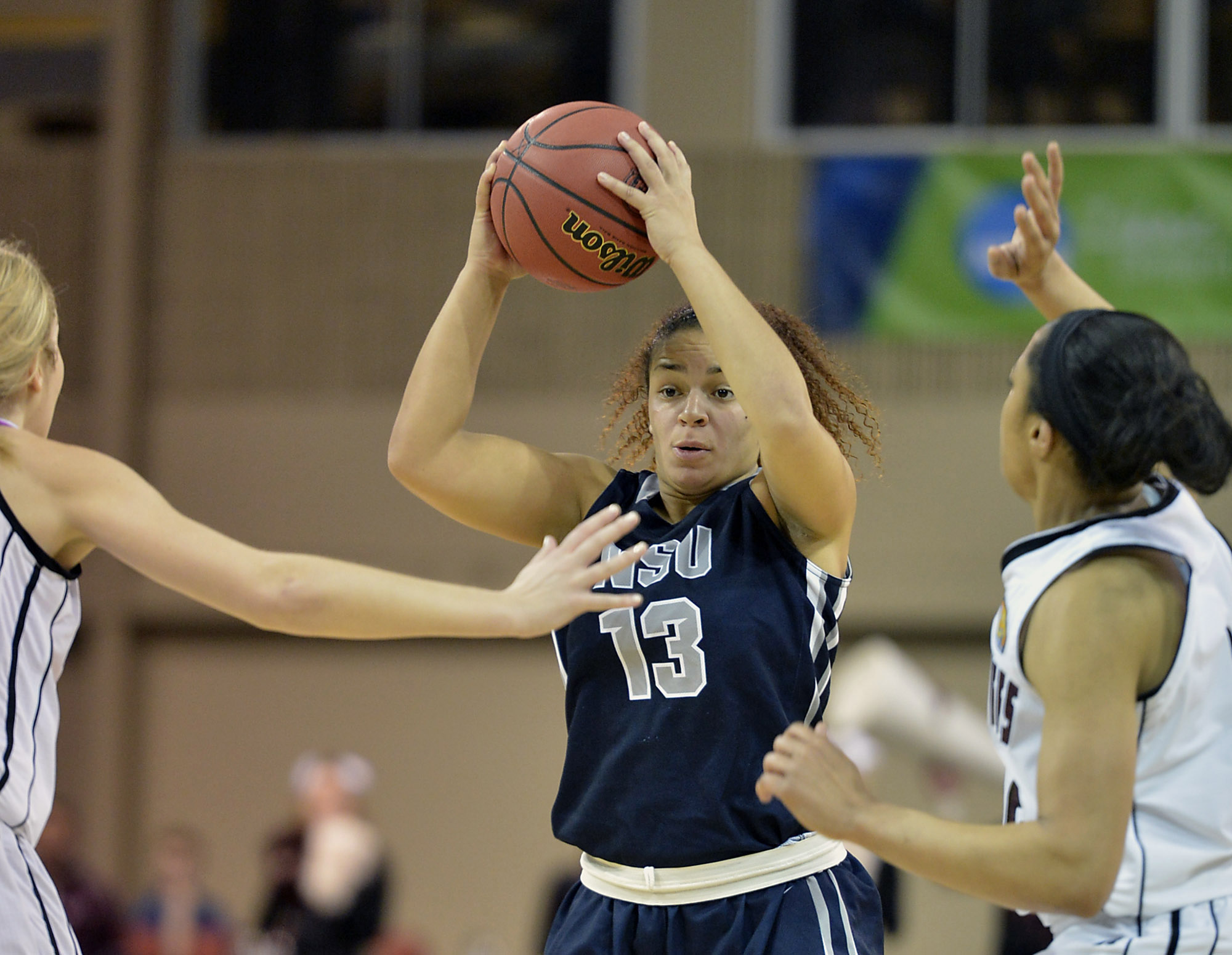 Nova Southeastern's Taylor Buie looks for an open teammate under pressure from West Texas A&M's Casey Land, left, and Devin Griffin, right, during the first half in an NCAA women's Division II basketball tournament semifinal in Erie, Pa., on Wednesday, March 26, 2014