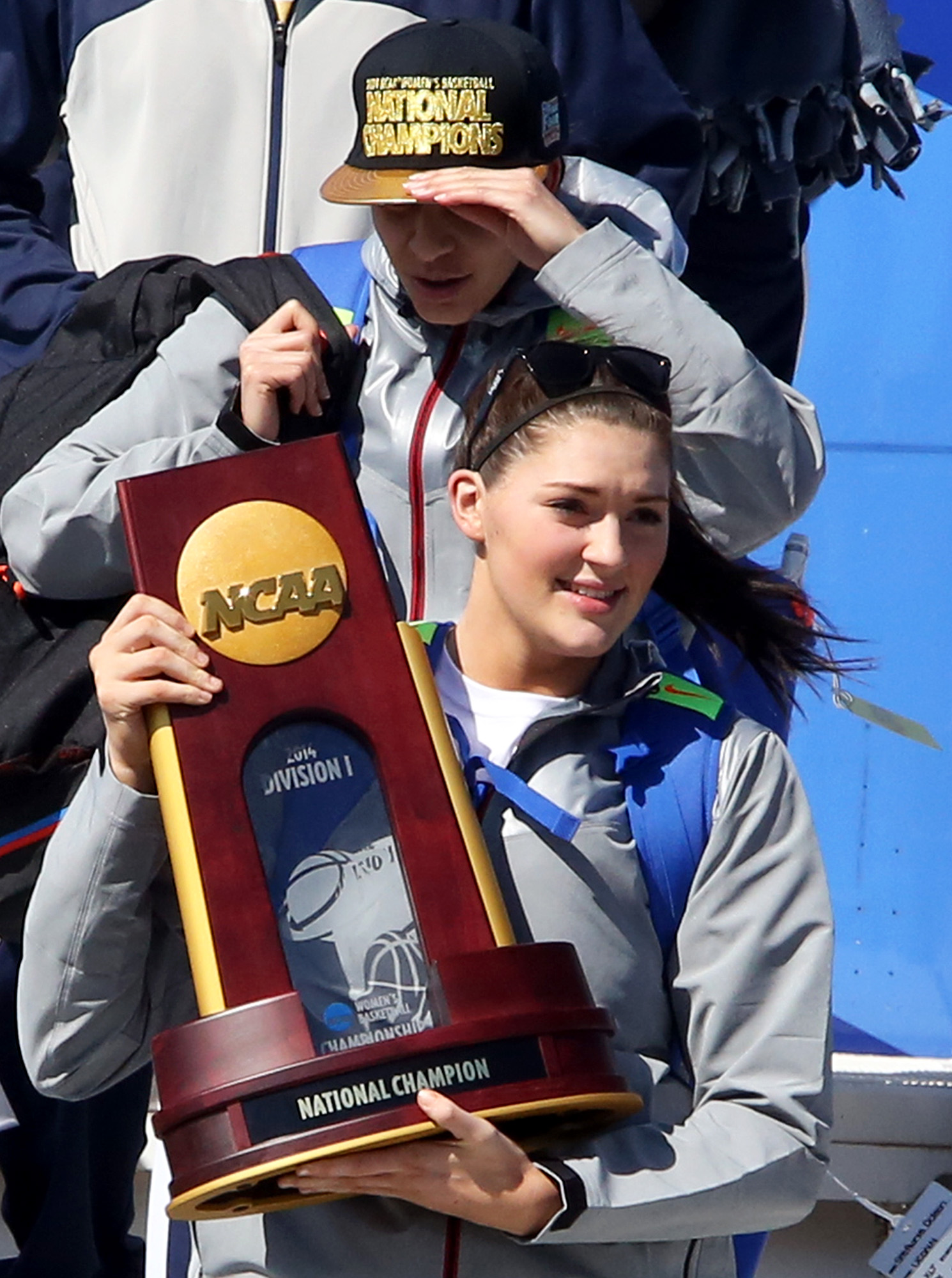 Connecticut's Stephanie Dolson holds the NCAA National Championship Trophy to fans as the team arrives at Bradley International Airport in Windsor Locks, Conn., Wednesday, April 9, 2014, the day after the Huskies defeated Notre Dame to clinch their ninth national championship