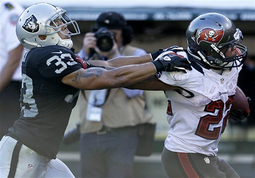 Doug Martin stiff arms Raiders DB Tyvon Branch as he runs for a 45-yard TD in the third quarter. (AP)