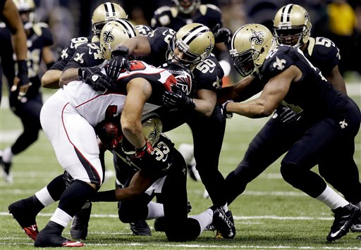 Falcons RB Michael Turner is stopped by Saints LB Curtis Lofton (50) and several teammates. (AP)