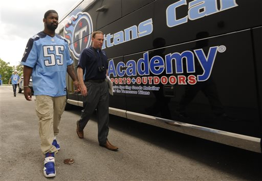 Tennessee Titans' Zach Brown (55) walks past the Titans Caravan bus with media relations employee Jared Puffer outside a sporting-goods store Wednesday, May 8, 2013, in Hixson, Tenn