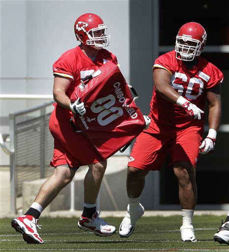 Kansas City Chiefs tackles Eric Fisher, left, and Steven Baker (60) participate in a drill during an NFL football training camp Tuesday, May 14, 2013, in Kansas City, Mo