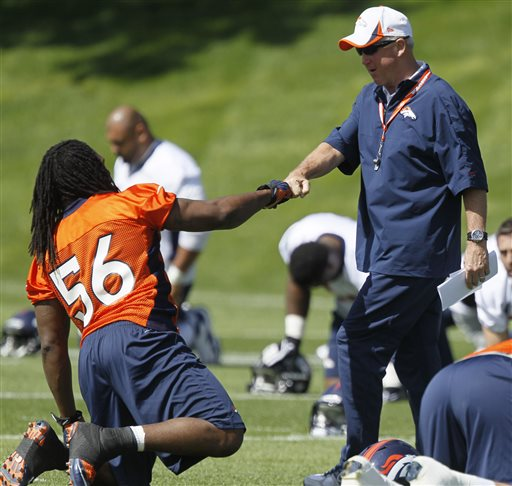 Denver Broncos head coach John Fox, right, greets middle linebacker Nate Irving during off season training camp at the NFL football team's training facility in Englewood, Colo., on Monday, May 20, 2013