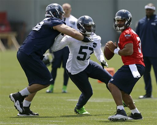 Seattle Seahawks quarterback Russell Wilson, right, looks to pass as Seahawks' Mike Morgan (57) is blocked by Seahawks' Breno Giacomini, left, Monday, May 20, 2013, during an organized team activity workout in Renton, Wash