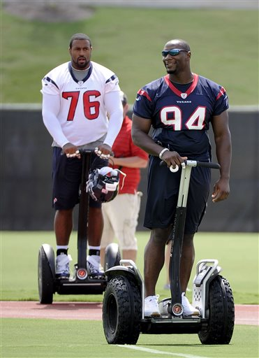 Houston Texans' Duane Brown (76) and Antonio Smith (94) arrive at the practice fields for the NFL football team's workouts Tuesday, May 21, 2013, in Houston