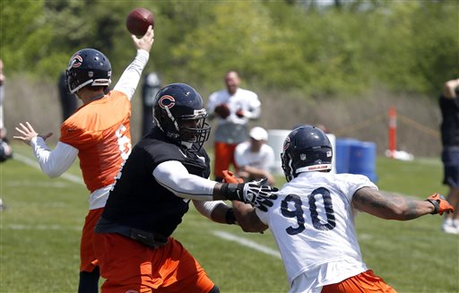 Chicago Bears offensive tackle Jermon Bushrod, center, keeps defensive end Julius Peppers away from quarterback Jay Cutler during the Bears' NFL football practice in Lake Forest, Ill., Tuesday, May 21, 2013