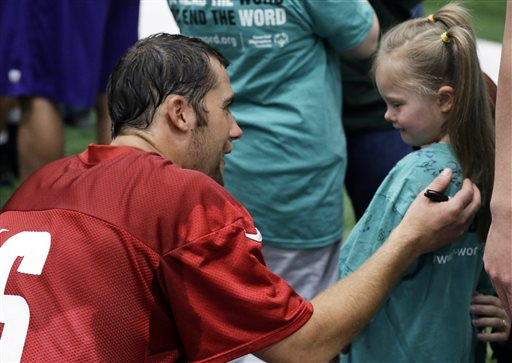 Minnesota Vikings backup quarterback Matt Cassel (16) talks to 9-year-old Kayla Tillison, of Farmington, Minn., after signing her jersey as the NFL football team hosted children from the Special Olympics after workouts, Wednesday, June 5, 2013, in Eden Prairie, Minn