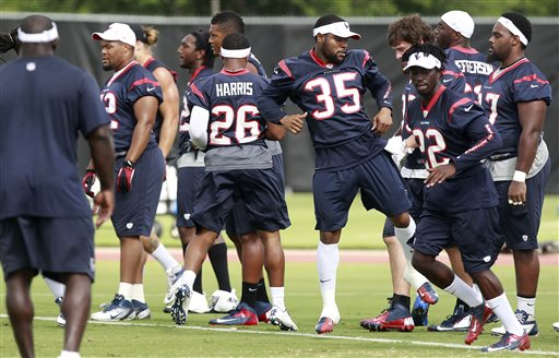 Houston Texans strong safety Eddie Pleasant (35), and cornerbacks, Brandon Harris, (26), and Roc Carmichael (22) warm up at an NFL football minicamp Tuesday, June 11, 2013, in Houston